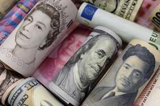"""Банкноты доллара США, евро, японской иены, китайского юаня, британского фунта и гонконгского доллара. Пекин, 21 января 2016 года. Россия может разместить евробонды в разных валютах несколькими траншами или единым в случае появления """"окна"""" на рынке, сказал глава департамента государственного долга российского Минфина Константин Вышковский журналистам в пятницу. REUTERS/Jason Lee"""