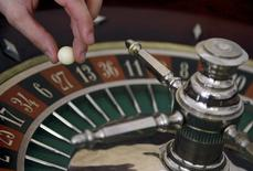 A young croupier trainee turns the roulette wheel at a gaming table at the Cerus Casino Academy in Marseille, France, in this picture taken on November 6, 2013.   REUTERS/Jean-Paul Pelissier/Files