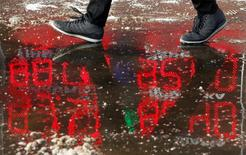 A pedestrian walks on a street as a board showing currency exchange rates is reflected in a puddle in Moscow, Russia, January 21, 2016. Russia's rouble fell further on January 20, setting a new record low of over 81 roubles per dollar as a bearish mood gripped Russian financial markets. REUTERS/Sergei Karpukhin