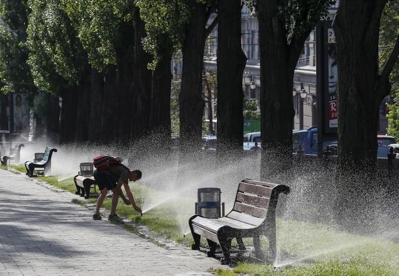 A man cools off in a water sprinkler in a park during a hot summer morning in central Kiev, Ukraine, July 24, 2015. REUTERS/Gleb Garanich