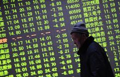 Un inversor camina junto a una pantalla electrónica que muestra información bursátil, en una correduría en Hangzhou, provincia de Zhejiang, China. 21 de enero de 2015. Las acciones chinas avanzaron el lunes, apoyadas por los valores de energía, luego de que los inversores mostraron cierto optimismo tras un repunte en los precios del petróleo y en los mercados bursátiles mundiales. REUTERS/China Daily