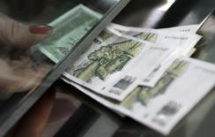 Кассир банка в Тбилиси протягивает лари. 1 февраля 2010 года. Грузинская валюта, лари, стабилизируется в ближайшее время и центробанк страны продолжит ужесточать денежно-кредитную политику в случае необходимости, сказал во вторник глава ЦБ Грузии Георгий Кадагидзе. REUTERS/David Mdzinarishvili