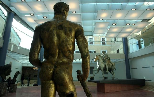 A gilded bronze Greek statue of Hercules (C) dated 300 BC, and equestrian statue of Marcus Aurelius, dating to the Roman emperor's reign, appear in their new hall at the Capitoline museum in Rome December 22, 2005.