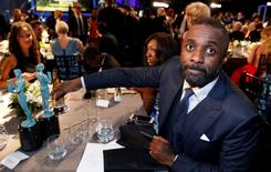 """Idris Elba sits with his two awards, one for Outstanding Performance by a Male Actor in a Television Movie or Miniseries for his role in """"Luther"""" and one for Outstanding Performance by a Male Actor in a Supporting Role for his role in """"Beasts of No Nation"""". REUTERS/Lucy Nicholson"""