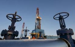 Нефтепровод напротив буровой установки на месторождении в Когалыме, принадлежащем компании Лукойл.  Цены на нефть снижаются после публикации неожиданно слабых экономических показателей Китая и Южной Кореи. REUTERS/Sergei Karpukhin