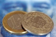 """Монеты 1 евро и 1 швейцарский франк. Цюрих, 8 августа 2011 года. Швейцарский франк остаётся """"значительно переоценён"""" по отношению к евро, и центральный банк Швейцарии по-прежнему готов вмешаться в случае необходимости и остановить укрепление валюты, сказал глава ЦБ во вторник. REUTERS/Christian Hartmann"""