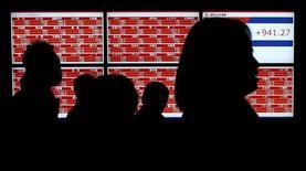 Люди у брокерской конторы в Токио. 22 января 2016 года. Японский индекс Nikkei опустился до недельного минимума в четверг, так как укрепление иены отрицательно сказалось на рыночных настроениях, в то время как акции Panasonic и Hitachi просели из-за того, что компании сократили прогнозы прибыли. REUTERS/Toru Hanai