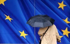 España, al igual que Francia, Italia y Portugal, están incumpliendo o podrían incumplir sus objetivos de consolidación fiscal a no ser que cambien sus políticas, según las previsiones económicas de la Comisión Europea divulgadas el jueves. En la imagen, una mujer con un paraguas camina junto a la sede de le Comisión Europea en Bruselas, el 2 de febrero de 2016.   REUTERS/Francois Lenoir