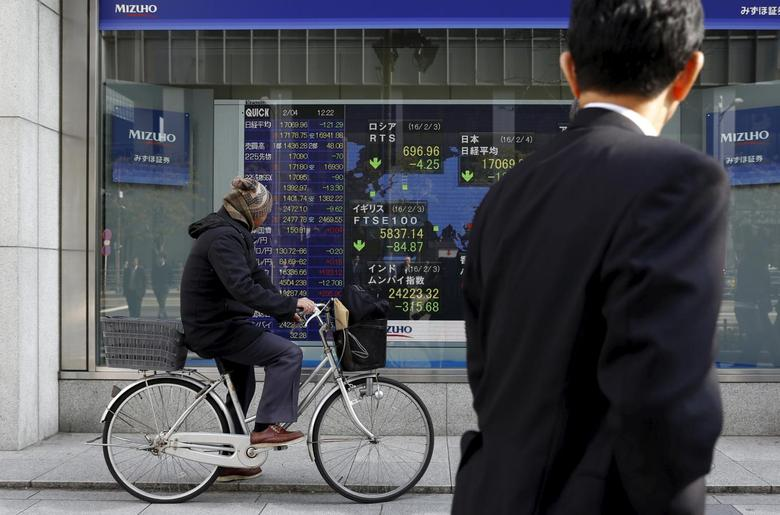 A man riding on a bicycle looks at an electronic board showing the stock market indices of various countries outside a brokerage in Tokyo, Japan, February 4, 2016.  REUTERS/Yuya Shino