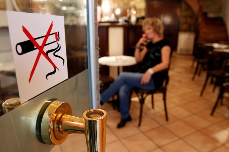 A woman smokes a cigarette behind a smoking ban sign in a restaurant-cafe in central Athens October 18, 2010.  REUTERS/John Kolesidis