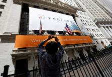 A woman takes pictures of the New York Stock Exchange, which has a Tableau Software banner on its facade, May 17, 2013.  REUTERS/Brendan McDermid