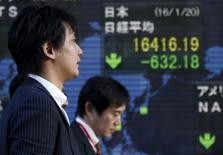 Un hombre camina junto a un tablero electrónico que muestra el índice Nikkei, afuera de una correduría en Tokio, Japón. 20 de enero de 2016. El índice Nikkei de la bolsa de Tokio registró el martes su mayor caída diaria en casi tres años en una sesión donde los papeles de los bancos se llevaron la peor parte de una ola de ventas, mientras que un yen más fuerte arrastró a las acciones en todos los ámbitos. REUTERS/Toru Hanai