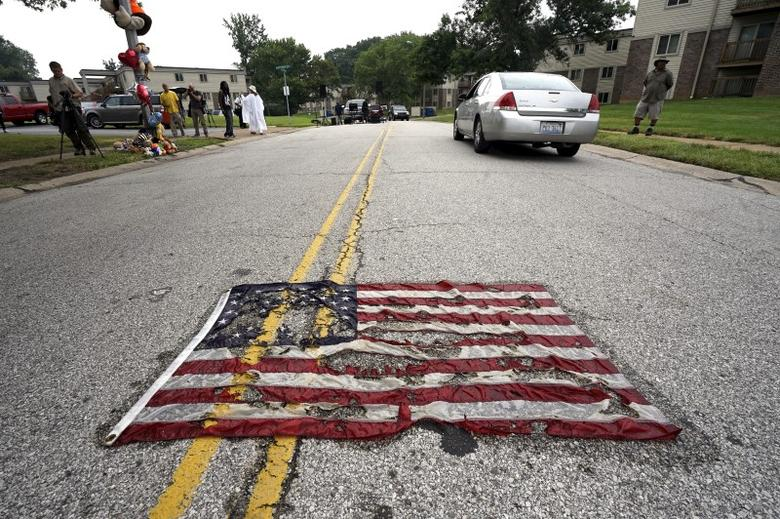 A partially burned American flag lies on the street near the spot where Michael Brown was killed before an event to mark the one-year anniversary of the his death in Ferguson, Missouri, August 9, 2015. REUTERS/Rick Wilking