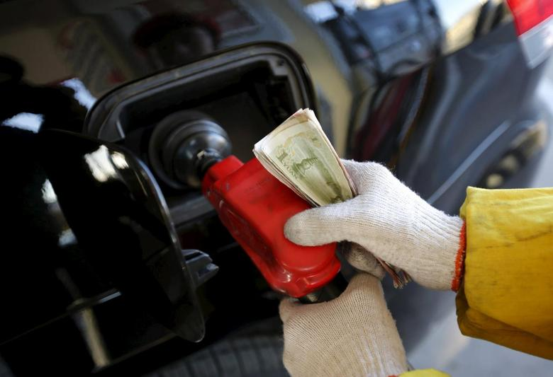 A gas station attendants holds money as he feeds fuel into a customer's car at a filling station in Beijing in the January 9, 2015 file picture. REUTERS/Kim Kyung-Hoon/Files