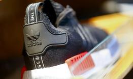 Adidas a relevé ses prévisions de chiffre d'affaires et de bénéfice d'exploitation pour 2016 après avoir dépassé ses objectifs de ventes et de résultats l'année dernière, l'équipementier sportif allemand semblant récolter les premiers fruits de sa vaste offensive commerciale. /Photo prise le 20 janvier 2016/REUTERS/Hannibal Hanschke