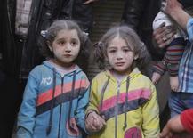 """Девочки, выжившие в результате того, что активисты назвали ударом ракет класса """"земля-земля"""" из расположения сил сирийского президента Башара Асада. Фото сделано в районе Алеппо 7 апреля 2015 года. Россия заявила в субботу, что согласованное мировыми державами за сутки до этого перемирие в Сирии, скорее всего, ждет провал. REUTERS/Abdalrhman Ismail"""