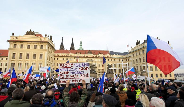 Demonstrators hold national flags and banners during an anti-immigrants rally in front of the Prague Castle in Prague, Czech Republic, February 6, 2016. The sign reads '' Stop Islam, stop migrants, this is our country''.   REUTERS/David W Cerny