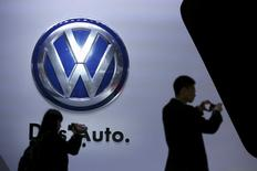 Guests stand next to a Volkswagen logo at the stage of the company at the 16th Shanghai International Automobile Industry Exhibition in Shanghai, in this April 20, 2015 file picture.  REUTERS/Aly Song/Files