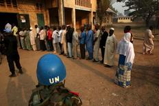 A United Nations security officer keeps guard as people wait in line to cast their votes during the second round of presidential and legislative elections in the mostly Muslim PK5 neighbourhood of Bangui, Central African Republic, February 14, 2016. REUTERS/Siegfried Modola