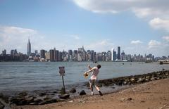 A man skips rocks along the East River in the Brooklyn Borough of New York, in this file photo taken July 22, 2012.  REUTERS/Keith Bedford/Files