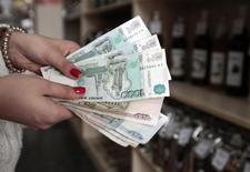 Продавец магазина в Ставрополе показывает рублевые банкноты. Рубль в плюсе на полуденных торгах среды за счет умеренного смещения баланса в пользу корпоративных продавцов валюты и при попытках нефти возобновить рост после падения накануне в ответ на решение ряда стран-производителей заморозить, а не сокращать её добычу. REUTERS/Eduard Korniyenko