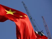 La bandera nacional de China delante de grúas en un distrito comercial en Pekín, China, 26 de enero de 2016. Las autoridades chinas regresaron del receso del Año Nuevo Lunar con un mensaje colectivo para los inversores nerviosos en el país y el mundo: Pekín pondrá un piso a la desaceleración de la economía, mantendrá su moneda estable y evitará que el empleo se debilite incluso en momentos en que reforma a sus industrias. REUTERS/Kim Kyung-Hoon