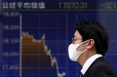 Las exportaciones interanuales de Japón sufrieron en enero su mayor caída desde la crisis financiera global, debido a un debilitamiento de la demanda en China y otros importantes mercados, dejando a la economía en una posición precaria tras una contracción en el cuarto trimestre. En la imagen, un peatón pasa junto a una pantalla con gráficos de cotizaciones en una casa de valores de Tokio, el 7 de enero de 2016. REUTERS/Yuya Shino