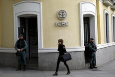 A woman walks past a Spanish Civil Guards at the headquarters of Industrial and Commercial Bank of China (ICBC) during a raid in Madrid, Spain, February 17, 2016. REUTERS/Juan Medina