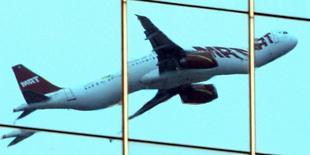 Самаолет отражается в окнах здания при вылете из аэропорта Сан-Паулу 7 декабря 2006 года. Количество бронирований авиабилетов в страны Латинской Америки и Карибского бассейна снизилось после того, как американское ведомство посоветовало беременным женщинам отказаться от поездок в районы распространения вируса Зика, сообщила в пятницу аналитическая компания ForwardKeys. REUTERS/Paulo Whitaker