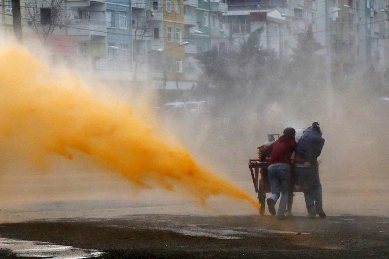 Street vendors take cover as Turkish riot police use a water cannon to disperse Kurdish demonstrators during a protest against the curfew in Sur district, in the southeastern city of Diyarbakir, Turkey February 21, 2016.  REUTERS/Sertac Kayar