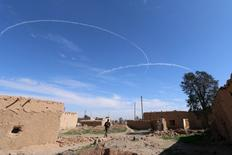 A Syria Democratic Forces fighter walks under contrails made by U.S. alliance air forces on the outskirts of al-Shadadi town, Hasaka countryside, Syria February 19, 2016.  REUTERS/Rodi Said