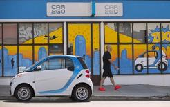 A man walks past an electric car from the car sharing company Car2Go, shown parked in front of their offices in San Diego, California September 1, 2015. REUTERS/Mike Blake -