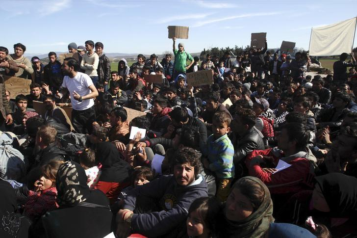 Refugees and migrants stage a protest next to a border fence at the Greek-Macedonian border, following a demand by Macedonia for additional identification from people seeking to cross the border and head to Western Europe, near the village of Idomeni, Greece, February 22, 2016. REUTERS/Alexandros Avramidis