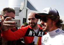 McLaren Formula One driver Fernando Alonso of Spain poses for a selfie with a supporter during the second testing session ahead of the upcoming season at the Circuit Barcelona-Catalunya in Montmelo, Spain, February 23, 2016. REUTERS/Sergio Perez