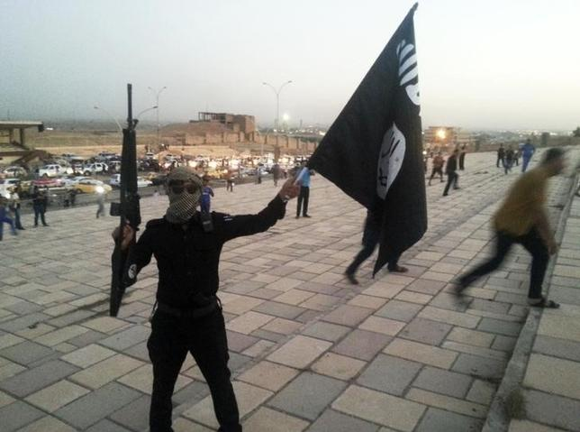 2月22日、イラク北部モスルを支配する過激派組織「イスラム国」戦闘員は、金融拠点に有志連合の爆撃機から攻撃を受けるなか、住民から金を搾り取るため米ドルとイラク・ディナールの為替レートを操作している。写真は同組織の戦闘員。モスルで2014年6月撮影(2016年 ロイター)