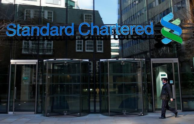 A man walks past the head office of Standard Chartered bank in the City of London February 27, 2015. REUTERS/Eddie Keogh