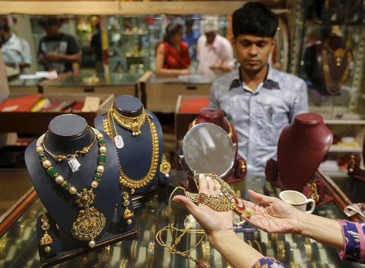 A customer tries a gold necklace at a jewellery showroom at a market in Mumbai, India, November 9, 2015. REUTERS/Shailesh Andrade/Files