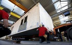 """Unos trabajadores construyen una casa prefabricada para los refugiados, en la compañía Bauer Holzsysteme, en Neukirch, Alemania, 7 de diciembre de 2015. El desempleo en Alemania descendió en febrero y la tasa de desocupación se mantuvo en mínimos post-reunificación gracias a un """"crecimiento económico moderado"""" en la mayor economía de Europa, dijo el martes la Oficina Federal del Trabajo. REUTERS/Michaela Rehle"""
