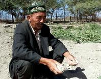 Нагмадин Жалмратов, 58-летний узбекский фермер, держит в руке комок сухой земли в селении Боршетау, Узбекистан, 22 сентября 2000 года. Президент Таджикистана, где находится основной источник воды в Центральной Азии, во вторник предупредил соседей об угрозе засухи ближайшим летом. PHOTOGRAPHER/Reuters Photographer