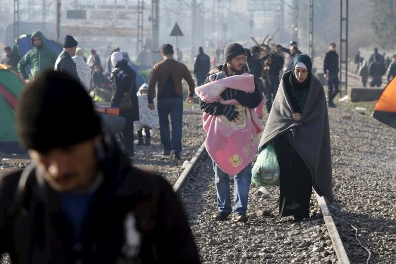 Migrants walk along railway tracks at the Greek-Macedonian border, near the village of Idomeni, Greece March 2, 2016. REUTERS/Marko Djurica