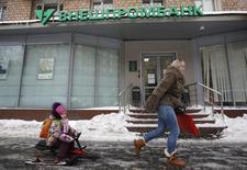 """Люди проходят мимо офиса Внешпромбанка в Москве 21 января 2016 года. """"Дыра"""" в балансе рухнувшего российского Внешпромбанка оценивается в 210 миллиардов рублей - это больше, чем изначально ее оценивал ЦБР, свидетельствует баланс банка на день отзыва лицензии - 21 января 2016 года. REUTERS/Sergei Karpukhin"""