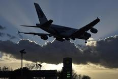 The UK Ј sterling price per litre of different blends of refined petrol (US $ 1.45 per litre unleaded) is seen at a BP  fuel station as a passenger plane makes it's final landing approach to Heathrow Airport in west London, Britain January 30, 2016. REUTERS/Toby Melville