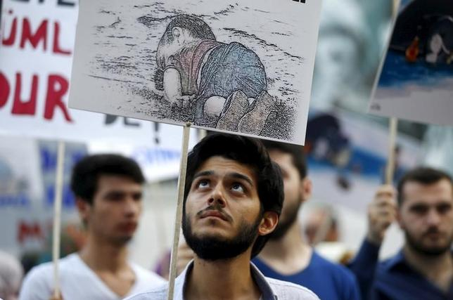 A man holds a poster with a drawing depicting a drowned Syrian toddler during a demonstration for refugee rights in Istanbul, Turkey, September 3, 2015. REUTERS/Osman Orsal