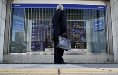 Un peatón mira un tablero electrónico que muestra los índices de mercado de varios países, afuera de una correduría en Tokio, Japón, 26 de febrero de 2016. Las bolsas de Asia tocaron máximos en dos meses el lunes, extendiendo las ganancias de la semana pasada, gracias a unos datos optimistas de empleo en Estados Unidos, un rebote en los precios del petróleo y una serie de garantías de los líderes chinos de que la economía continúa sobre una base firme. REUTERS/Yuya Shino