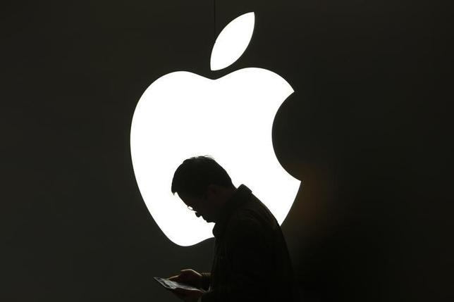 A man looks at his Apple iPad in front an Apple logo outside an Apple store in downtown Shanghai March 16, 2012. REUTERS/Aly Song