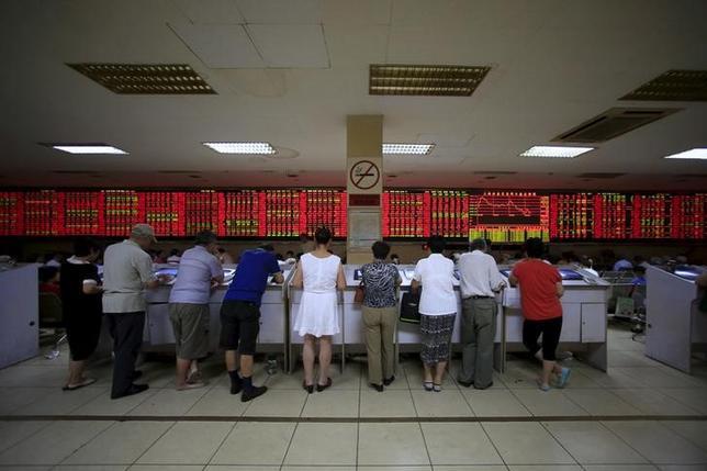 3月9日、昨年の春節には羽振りが良かった中国の証券会社だが、株式市場の暴落を経て今年はすっかり緊縮ムードに転じている。写真は上海の証券会社で株価を見入る個人投資家。昨年9月撮影(2016年 ロイター/Aly Song)