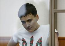 Бывшая военнослужащая украинских ВВС Надежда Савченко смотрит из стеклянной клетки в зале суда в Донецке Ростовской области 9 марта 2016 года. Отказавшаяся от воды и пищи в знак протеста против российского суда 34-летняя украинка может умереть до приговора на процессе, в котором выступает обвиняемой в убийстве двух журналистов, сообщил адвокат. REUTERS/Stringer