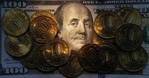 Рублевые монеты на долларовой купюре в Санкт-Петербурге 22 октября 2014 года. Рубль в четверг обновил максимумы текущего года после решения ЕЦБ понизить ключевую процентную ставку до нулевой отметки и расширить программу денежного стимулирования, что предполагает снижение стоимости фондирования операций с высокорискованными активами. REUTERS/Alexander Demianchuk