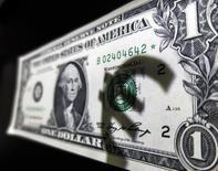 День символа валюты евро на долларовой купюре в Мадриде 10 марта 2015 года. Евро просел к доллару после того, как Европейский центральный банк решил подстегнуть экономику и потребительские цены снижением ключевой процентной ставки и расширением скупки активов, что стало неожиданностью для рынков. REUTERS/Sergio Perez