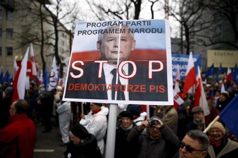 A man holds a banner with Jaroslaw Kaczynski, leader of ruling party Law and Justice (PiS) with the slogan ''Program of the party program of the nation, Stop Demoktaturze (combine words democracy and dictatorship) of PiS'' as he takes part in march demanding their government to respect the country's constitution in front of the Constitutional Court in Warsaw, Poland, March 12, 2016. REUTERS/Kacper Pempel